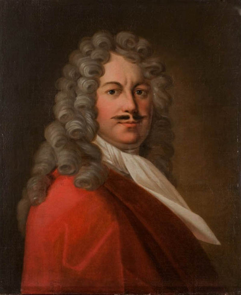 Porträtt av man med argrynka i pannan och tunn svart mustasch. Klädd i röd rock, vit halsduk. På huvudet, stor gråaktig 1700-tals peruk.