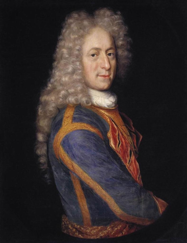 Porträtt av blek man med mörka ögon. Iklädd blå rock med vitt krås. På huvudet stor, krullig och ljusblond 1700-tals peruk.