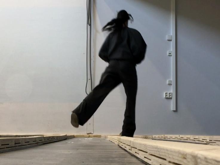 En dansare klädd i svart sett ur lågt perspektiv mot en grå vägg