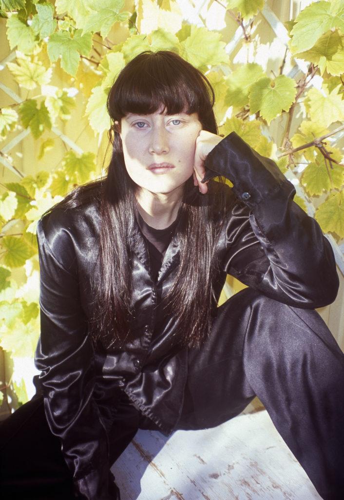 En svartklädd kvinna mot en ljusgrön bakgrund av löv. Emma Strandsäter, foto Caroline Nord