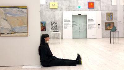 En kvinna i svarta kläder sitter på golvet i en stor ljus utställningssal. Hon lutar sig mot kanten av en vägg. Man anar tavlor och föremål omkring henne.