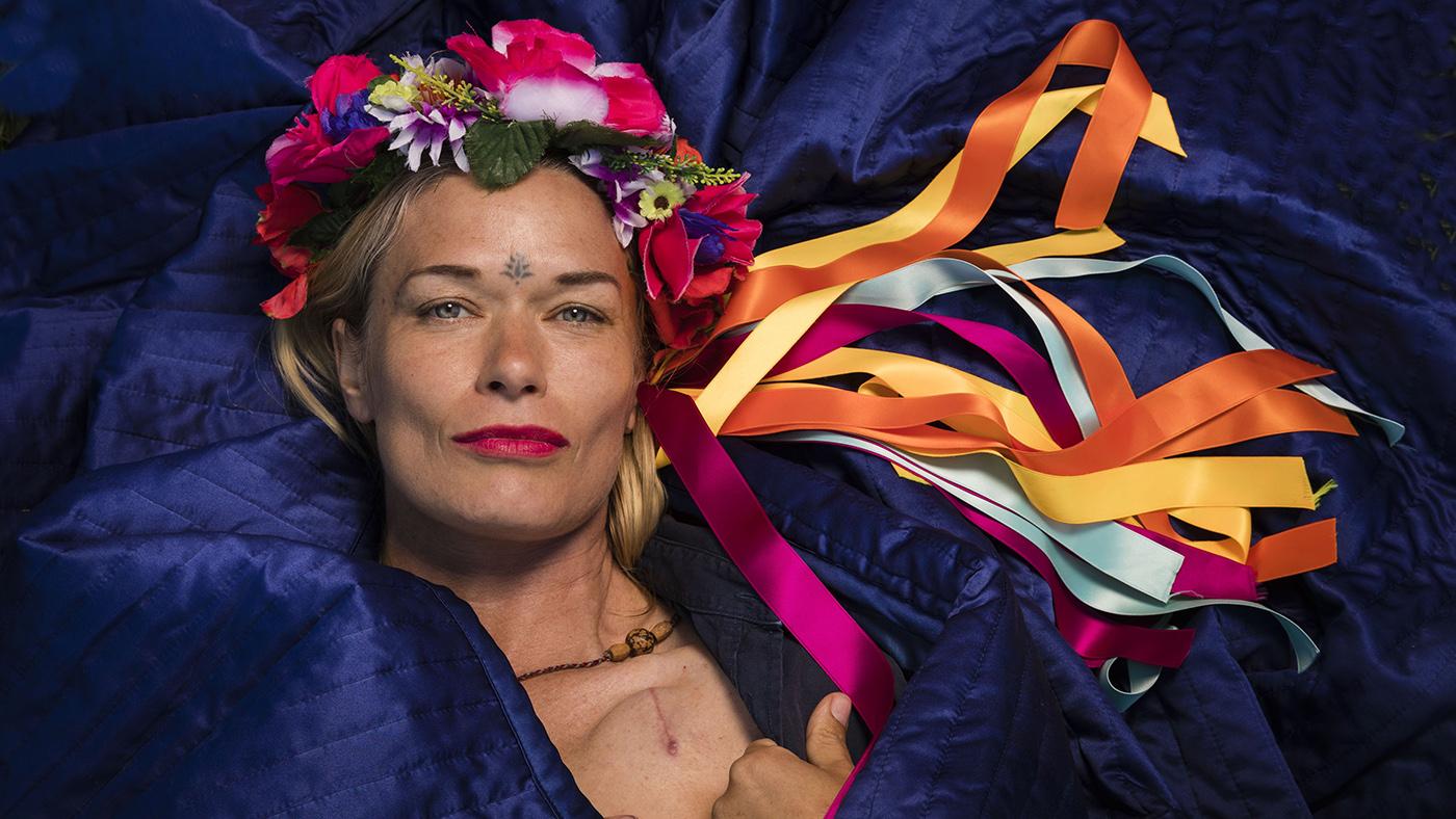 En kvinna med blomsterkrans och sidenband i många färger ligger på en blå textil. Foto Juan De Dios.