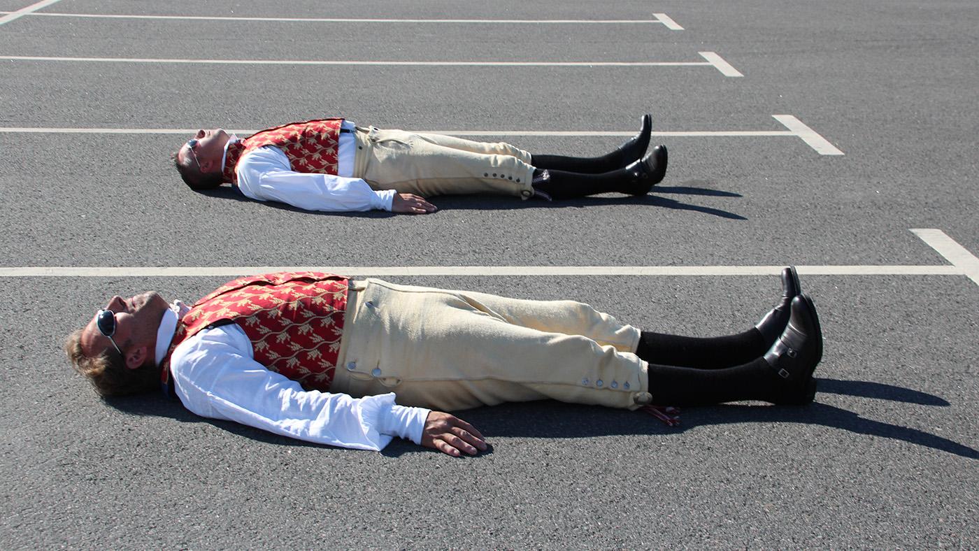 Två män iklädda häradsdräkter ligger på en parkering