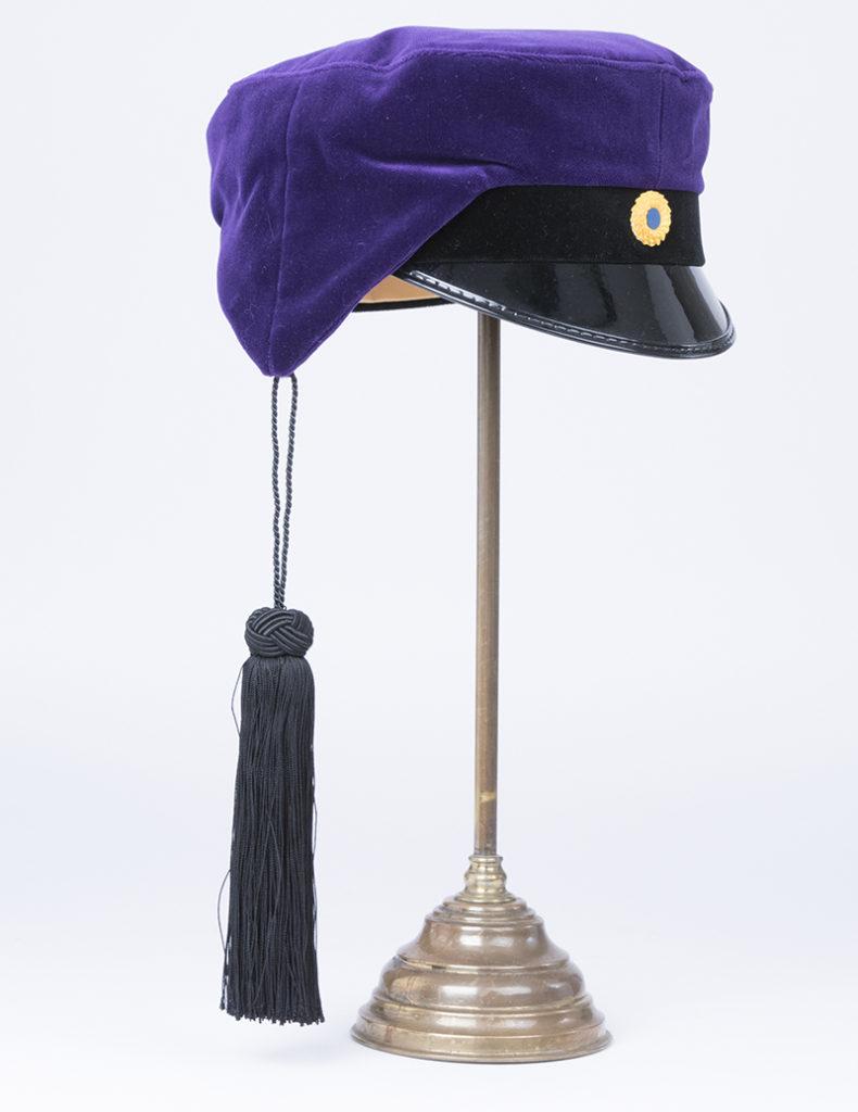 Studentmössa, så kallad teknologmössa av lila sammet och svart hängande tofs.
