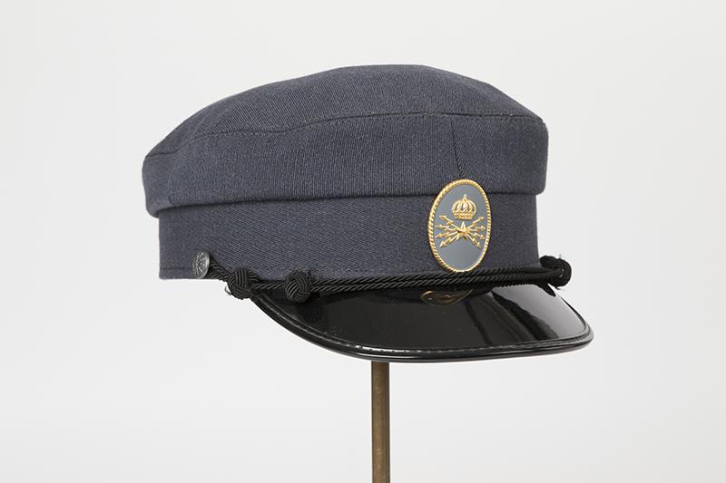 Skärmmössa (keps) med lackskärm med Televerkets emblem och snoddar framtill på mössan.