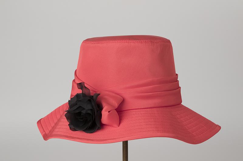 Rosa-röd damhatt av acetat, med hög, rak kulle, vågigt helstickat brätte, som är bandkantat av samma tyg. Monterad med en drapering med en svart blomma.