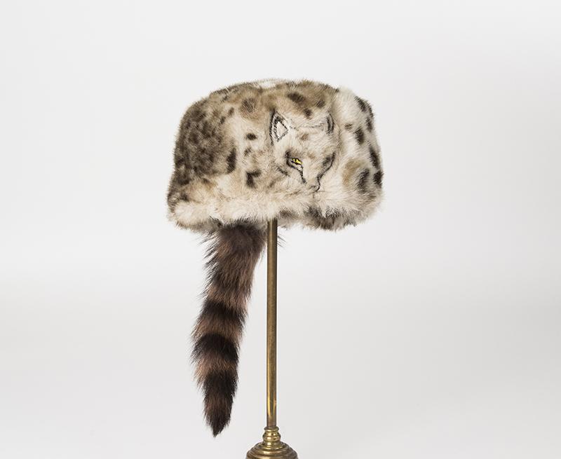 Barnmössa av leopardmönstrad fuskpäls, framtill på mössan är ett rävhuvud broderat. Bak på mössan är en tvättbjörnsvans påsydd.