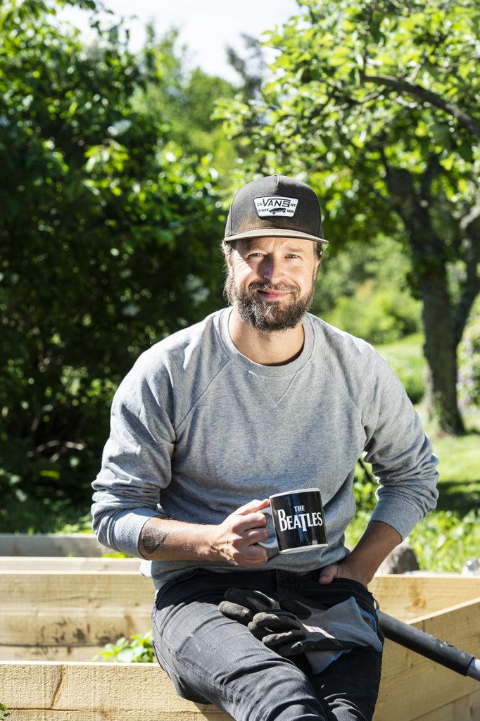 En glad man iförd keps och grå tröja håller en kopp och sitter ute i trädgården. Foto: Anna Hållams