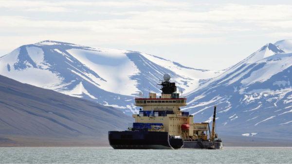 Isbrytaren Oden vid Svalbard. Bergstoppar med snö i bakgrunden.