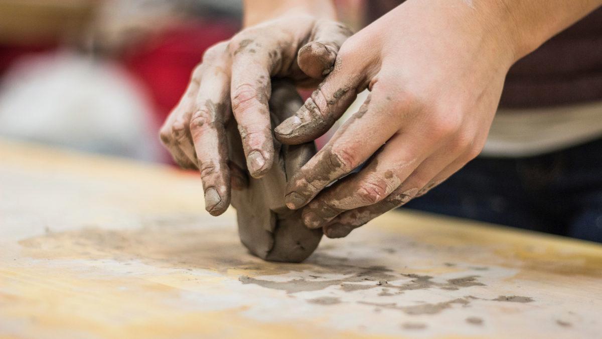 Händer som formar lera.
