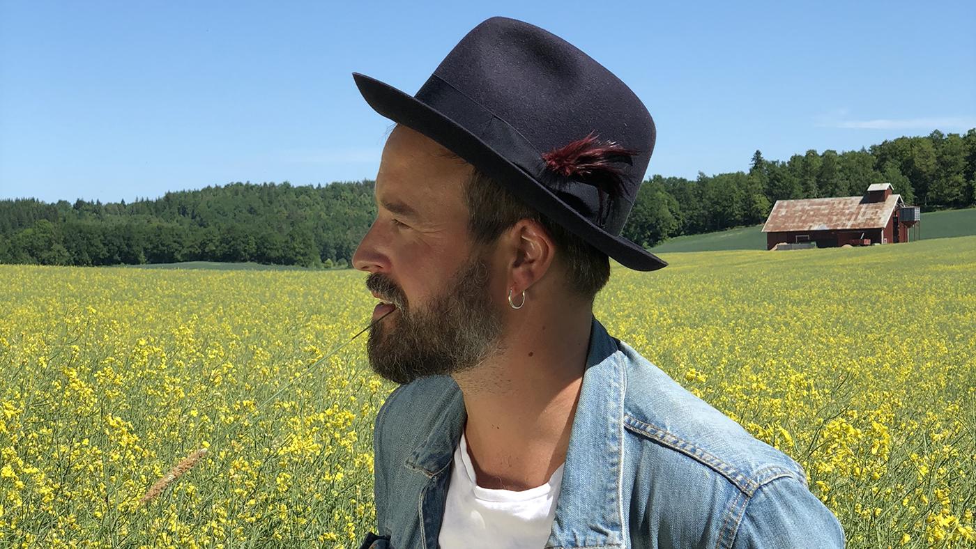 En man iklädd hatt och jeansskjorta står vid ett rapsfält och tittar åt sidan. Foto: Anna Hållams