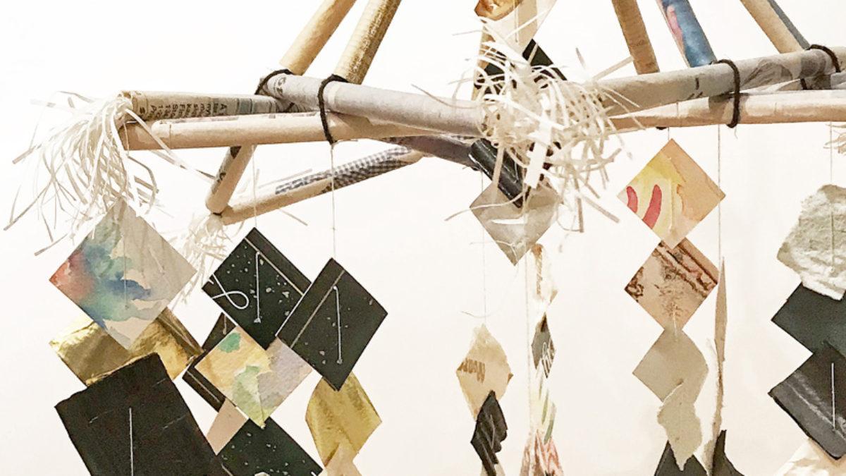 Små bitar av färgat papper fästa på trådar som i sin tur är fästa vid korslagda grenar.