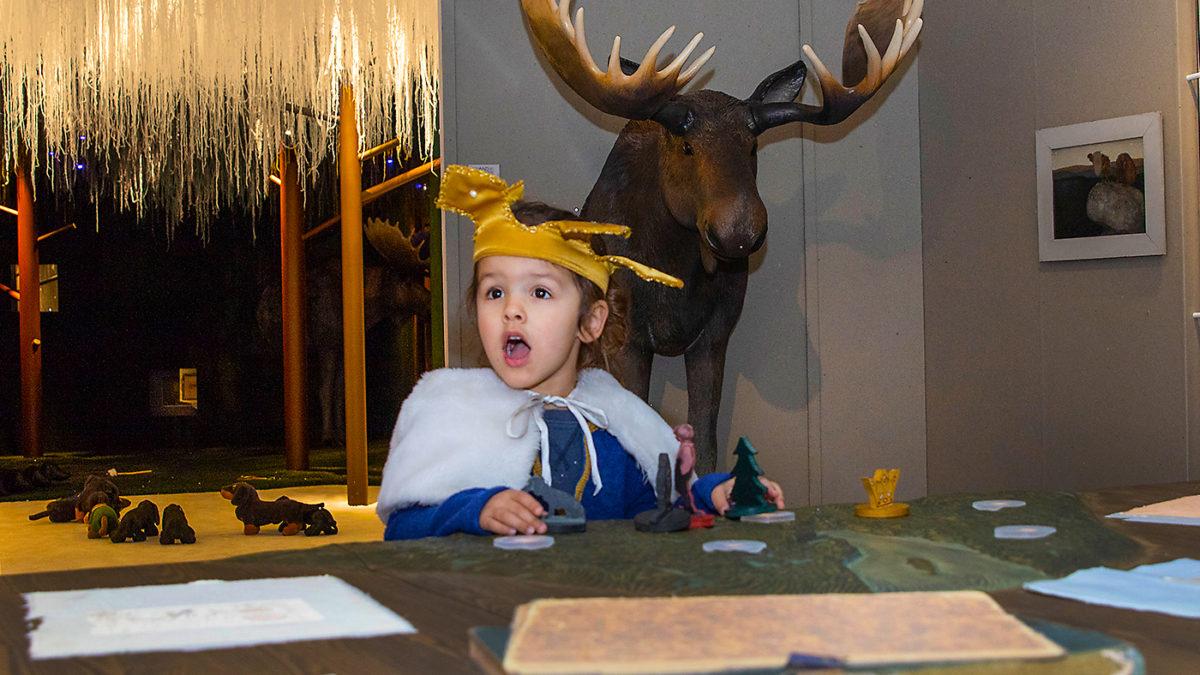 Barn leker vid en skiss-karta i utställningen Följa John