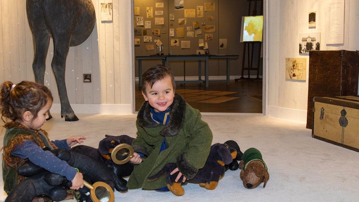Två barn leker med mjukistaxar och förstoringsglas i ett vitt rum i utställningen Följa John