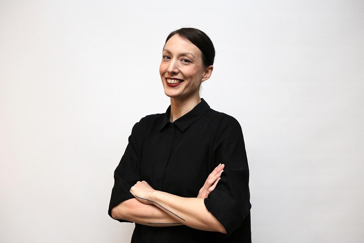 En glad kvinna klädd i svart blus. Foto Ninni Westin