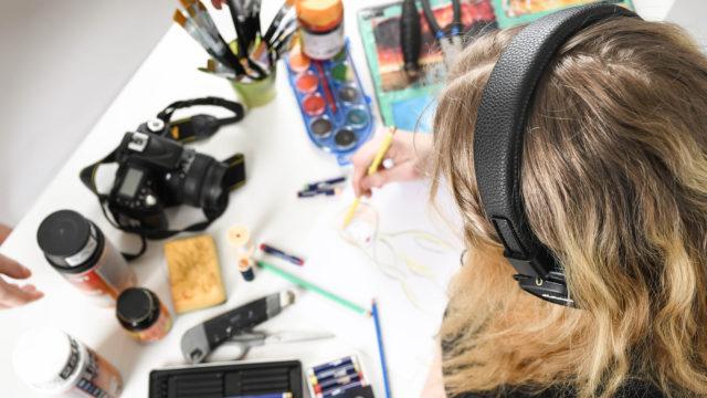 Ett skrivbord sett uppifrån fyllt med penslar, pennor, färg, verktyg, en kamera. Man anar en person med hörlurar på som sitter och tecknar.