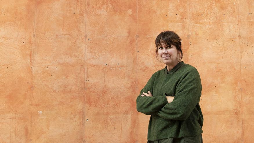 En kvinna i grön tröja framför en terracottafärgad betongvägg