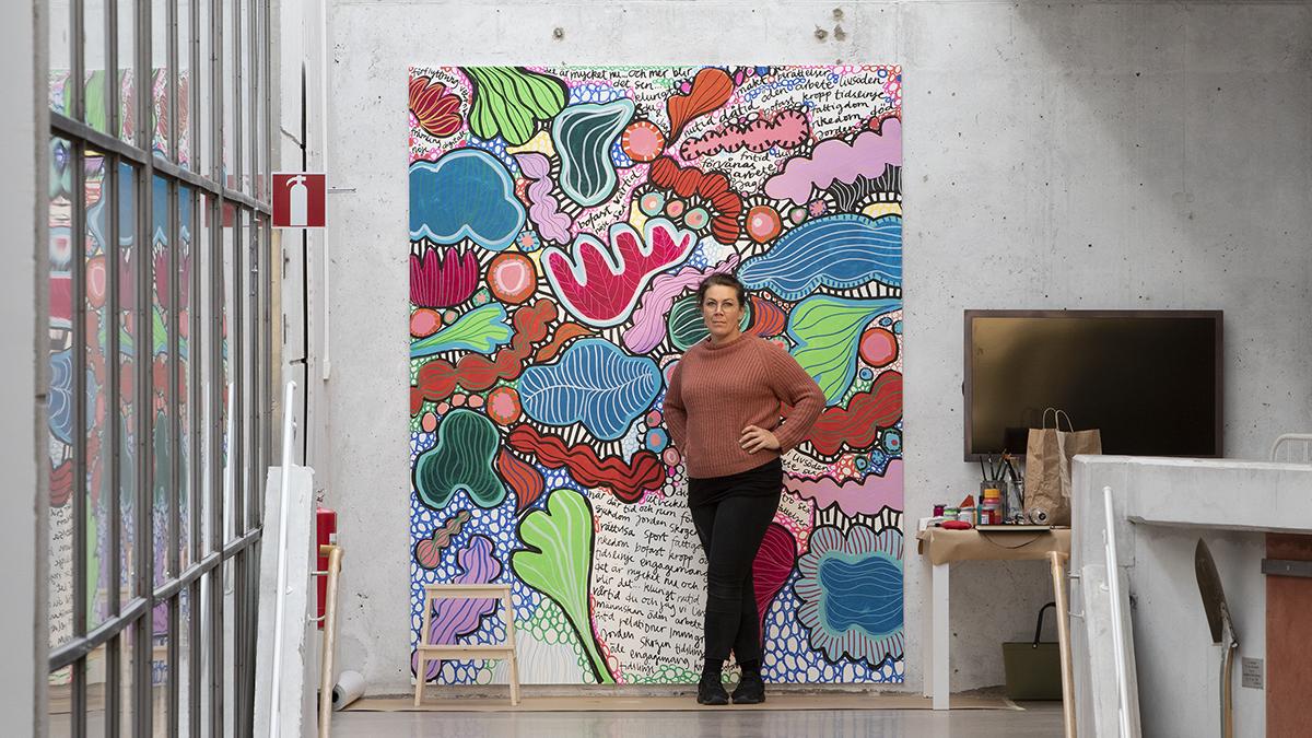 Konstnären Annefrid Sjöman står framför sitt verk som är sprakande former och färger med ord antecknade inuti.