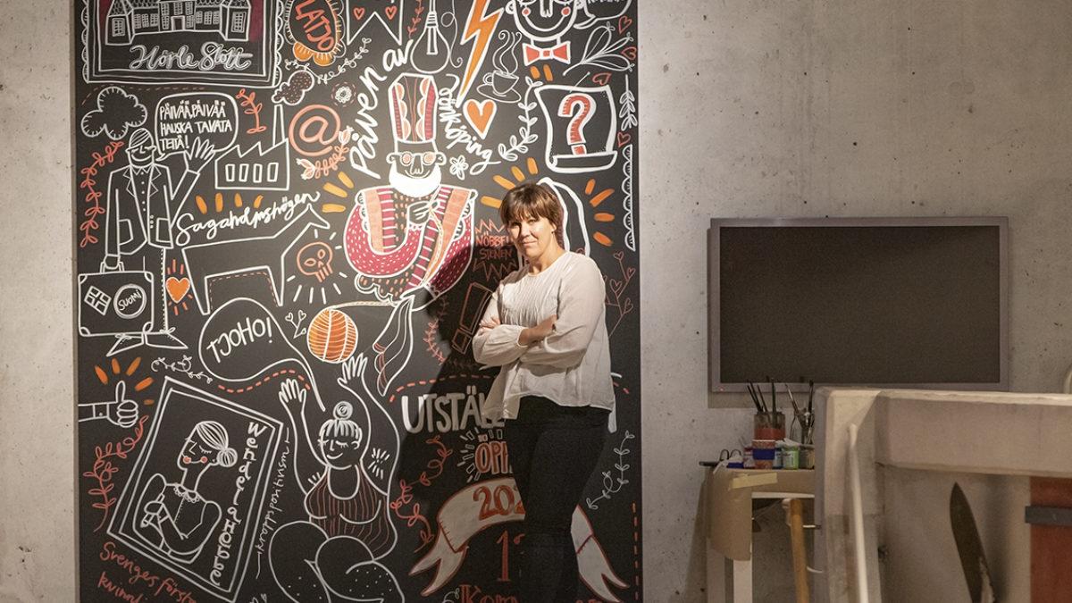 Konstnären Annefrid Sjöman står framför sin färdiga illustration, där mängder av figurer och symboler i vitt, rosa och orange syns på en svart bakgrund.