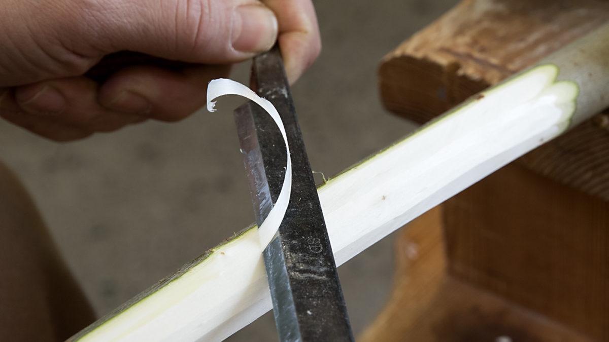 Man ser en hand som täljer på en bit trä med kniv.