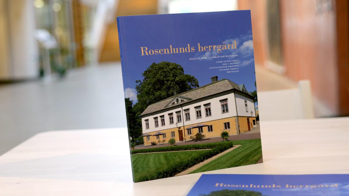 En bok står uppställd på ett bok inne i museets entréhall. Det står Rosenlunds herrgård på den i gult. Fotot på omslaget visar herrgårdsbyggnaden i sin helhet, med blå himmel bakom.