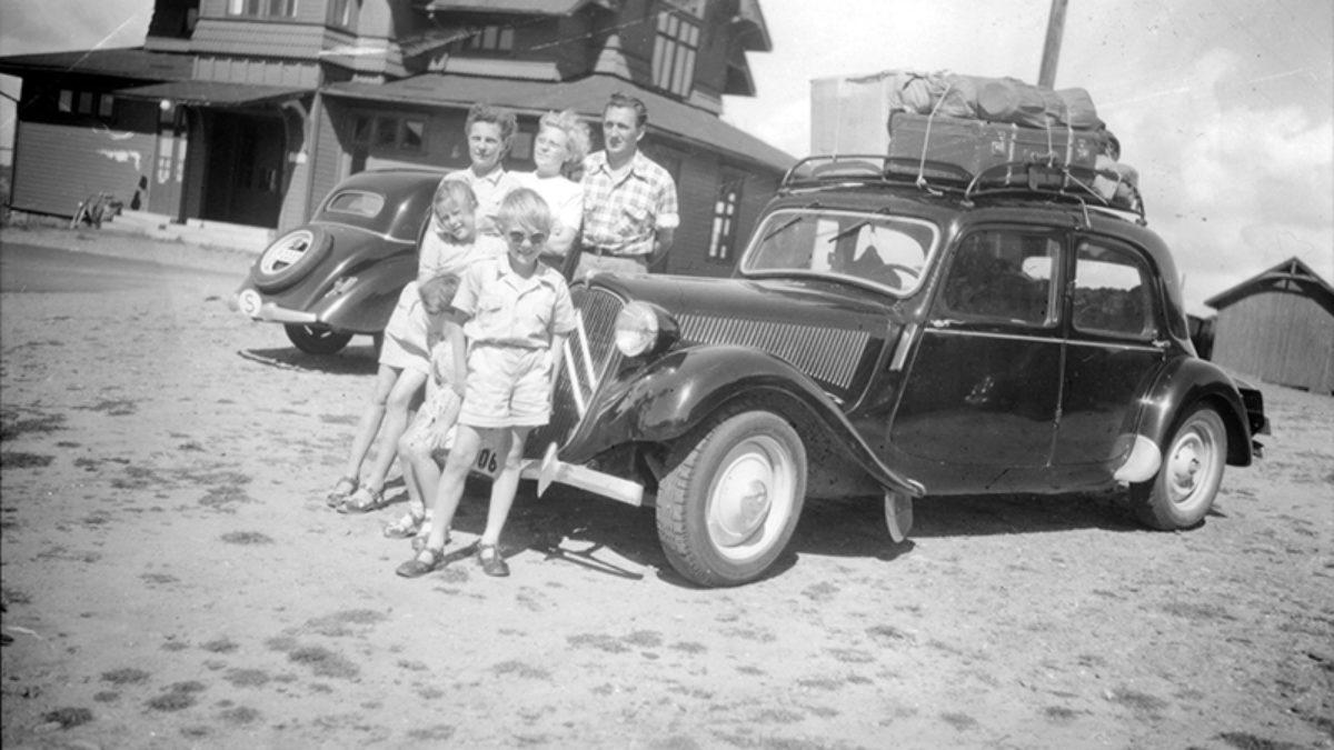 Bilsemester. Tre vuxna personer och tre barn står framför en bil med packning fastsurrad på taket.