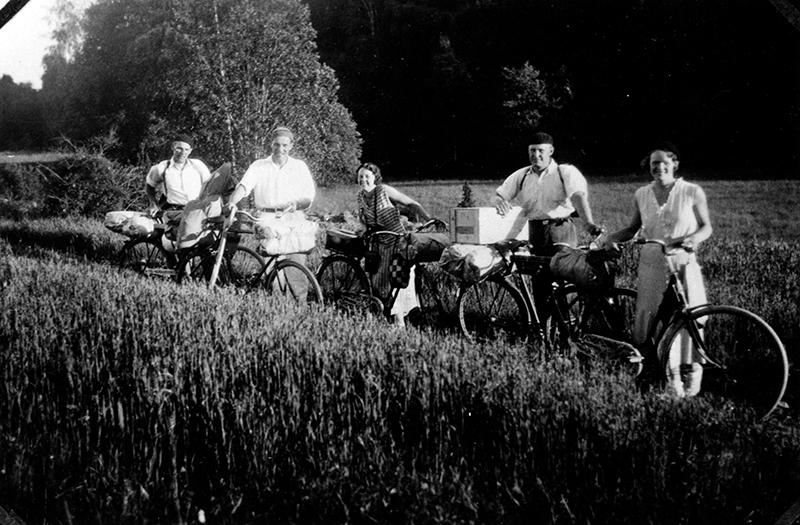 Cykelutflykt. Fem personer står på en rad med varsin cykel. Cyklarna är lastade med packning.