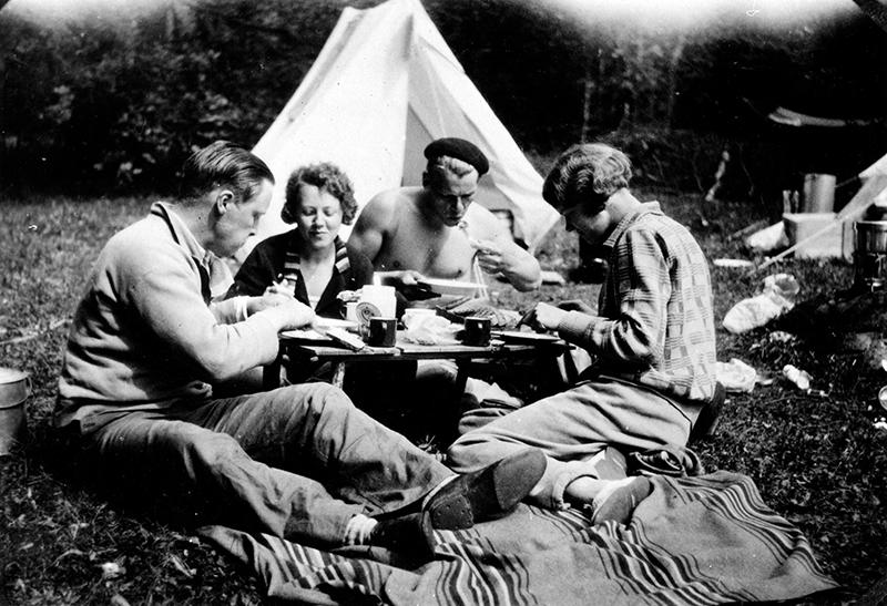 Tältsemester. Två kvinnor och två män sitter framför ett litet tält och äter mat.