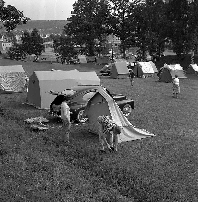 Campingplats. Två personer sätter upp ett tält.