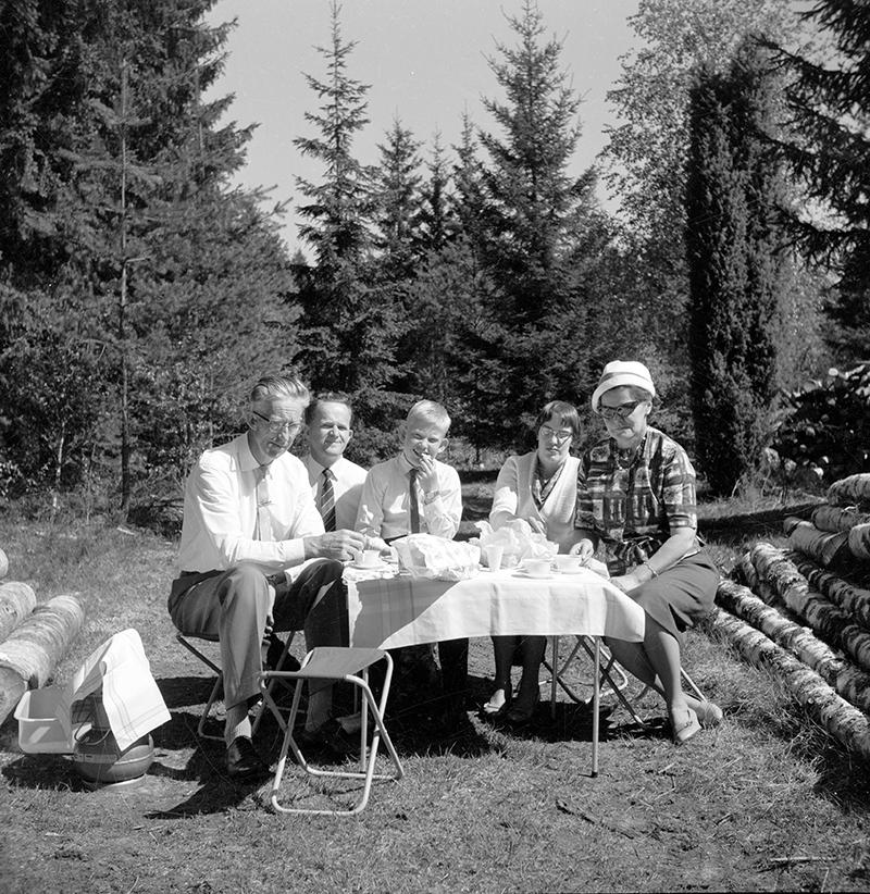 Fem personer sitter runt ett dukat bord intill en skog.