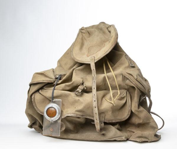 Äldre modell av ryggsäck med päronformad säck av kraftigt grå-brunt tyg. På ryggsäcken hänger ett kompass.