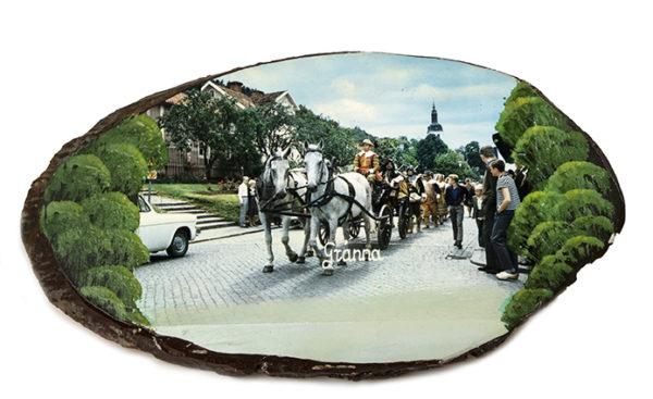 Björktavla, snedsågad björkstam med ett monterat fotografi. Motivet är från Gränna där ett hästekipage passerar på huvudgatan.