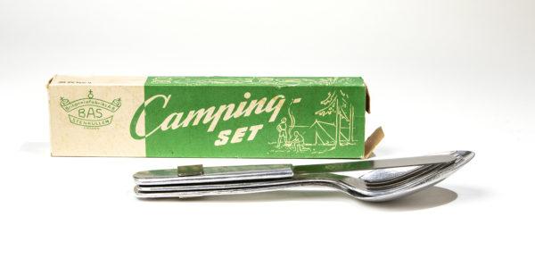 Campingbestick: sked, gaffel och kniv av metall sitter ihop. Bakom besticken syns den gröna originalkartongen.