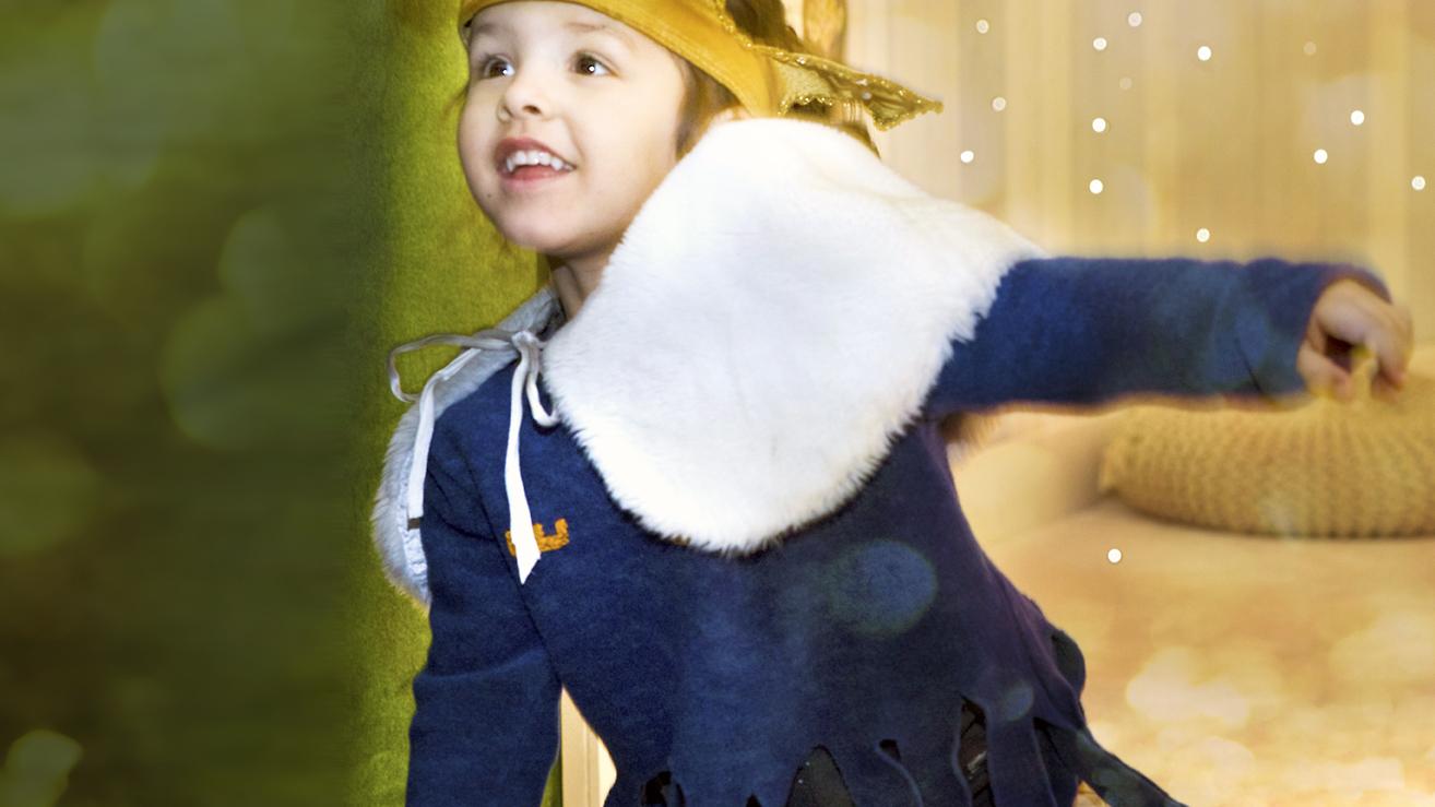 Ett barn utklädd i krona och mantel springer förbi, bakgrunden glittar