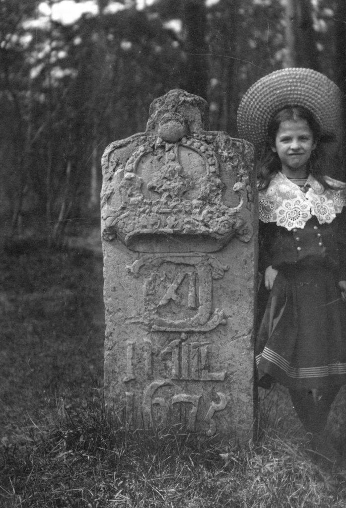 Äldre svartvitt foto med milsten och flicka i tidsenlig dräkt och hatt.