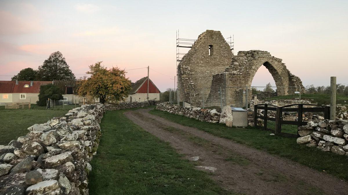Ruin av en stenbyggnad, en grusväg och en stenmur