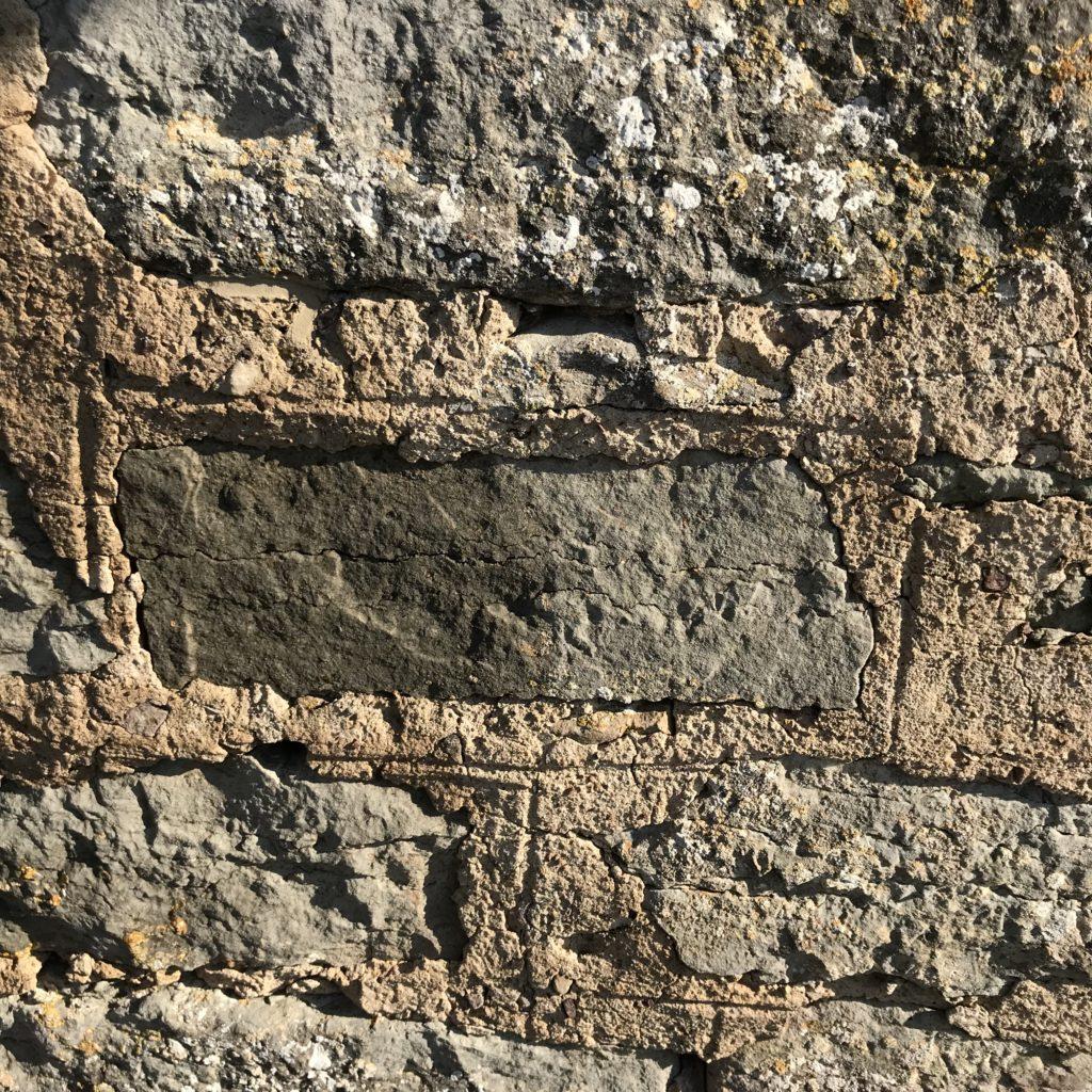 Närbild av stenar och fogbruk i en murad vägg