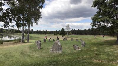En ring med stenar. I bakgrunden syns flera golfspelare.