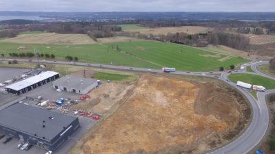 Drönarbild med översikt över utgrävd yta mellan trafikerad väg och industribyggnad.