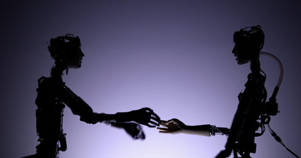 Två robotliknande skulpturer vars händer rör varandra