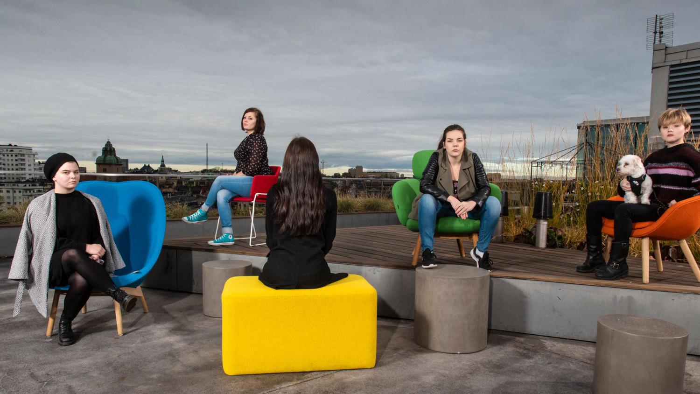 Fem personer sitter utspridda i en takmiljö i betong