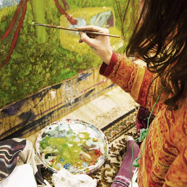 En person med pensel framför en olje/akrylmålning i gröna toner