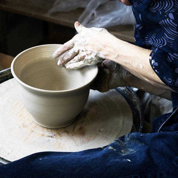 Händer formar en skål i lera på en drejskiva