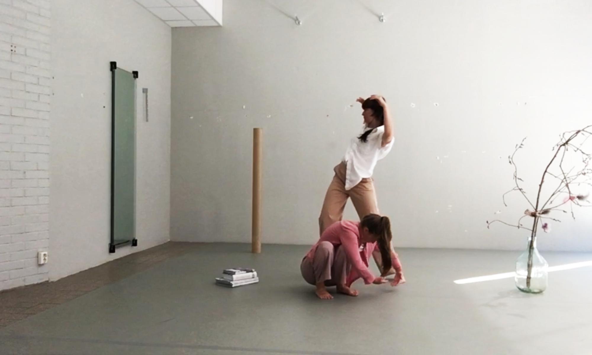 Två dansare i ett utställningsrum, den ena stående och den andra sittande på huk.