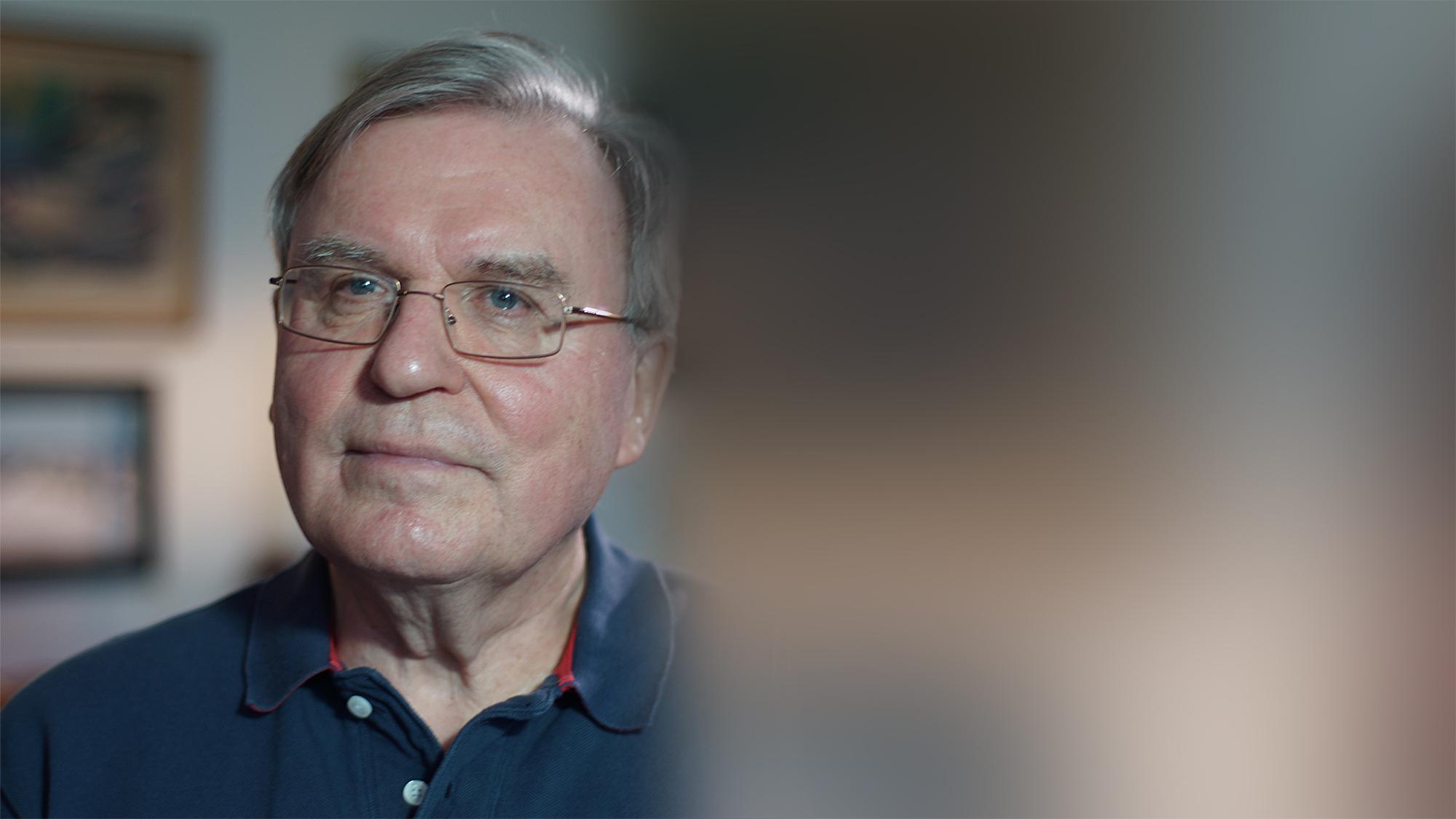 Ett porträtt av en gråhårig man i glasögon och blå skjorta