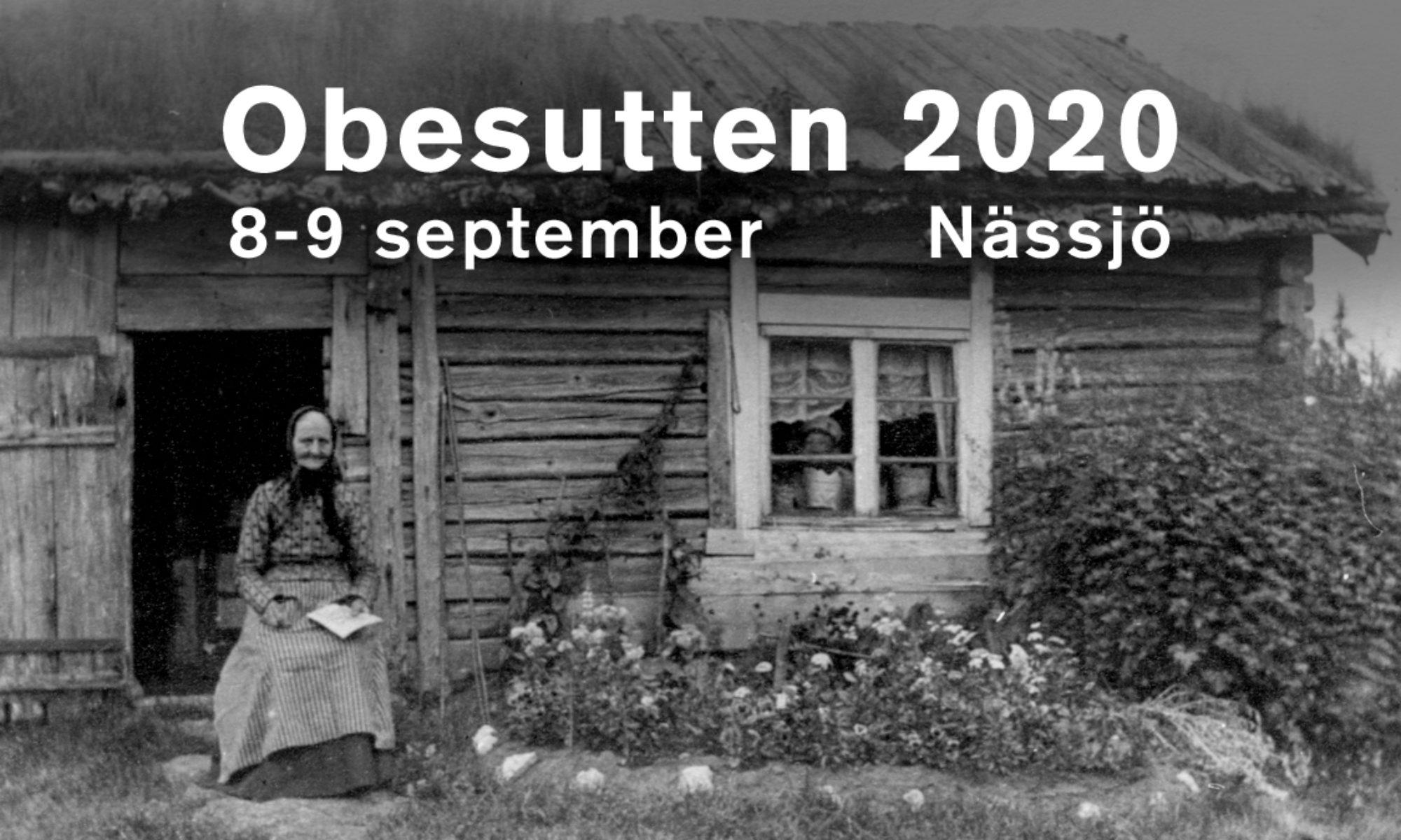 En svartvit äldre bild där en äldre dam sitter utanför en enkel stuga, intill en prydnadsrabatt.