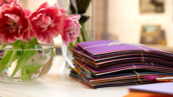 Färgranna pappersark ihopbuntade bredvid en vas med tulpaner