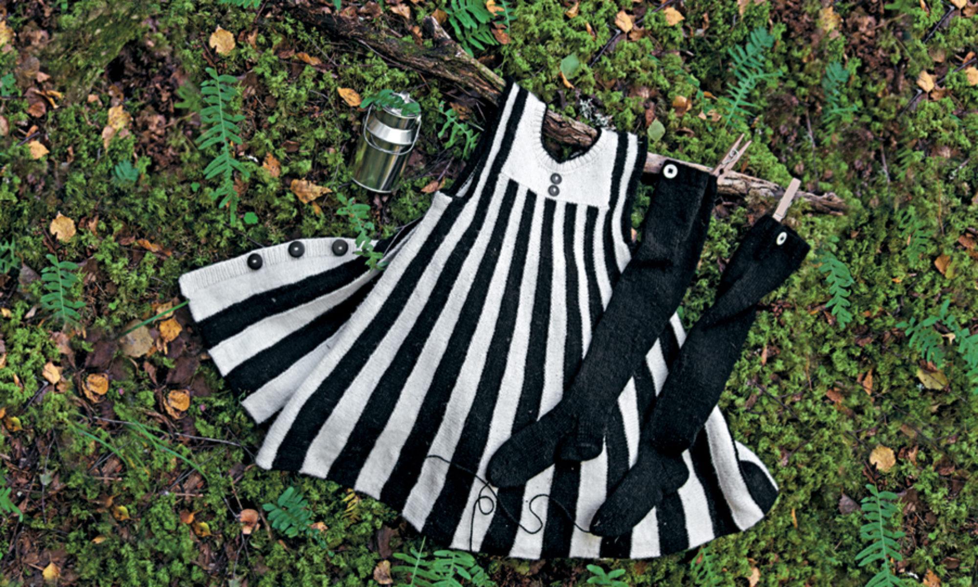 En bild på en svartvit stickad klänning som ligger utspridd på mossa i skogen