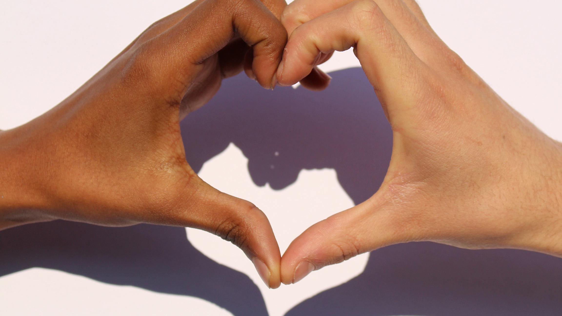 Två par händer med olika hudfärg formar ett hjärta mot en vit bakgrund