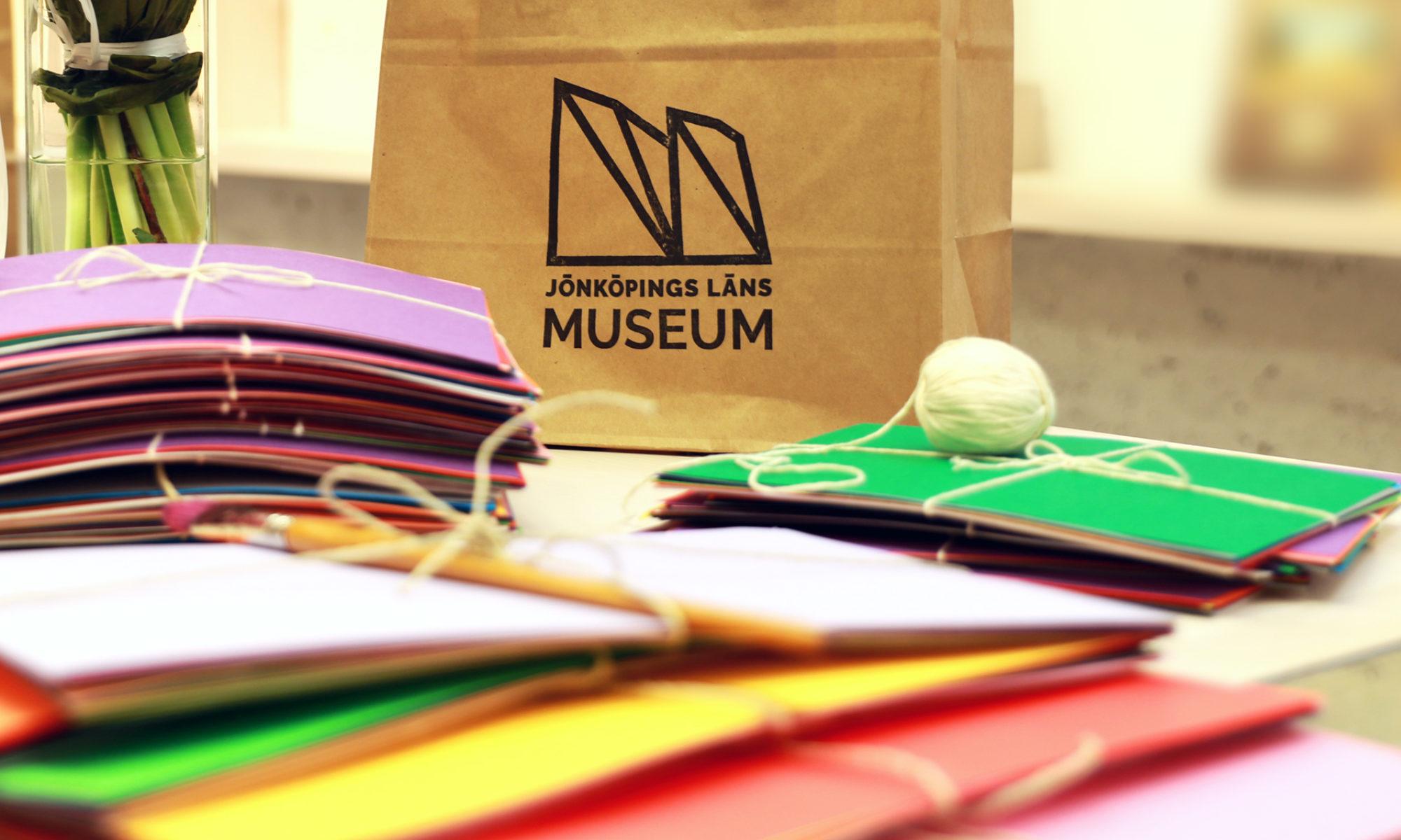Pappersark i olika färger i högar, en rulle med snöre och en papperspåse med museets logotyp